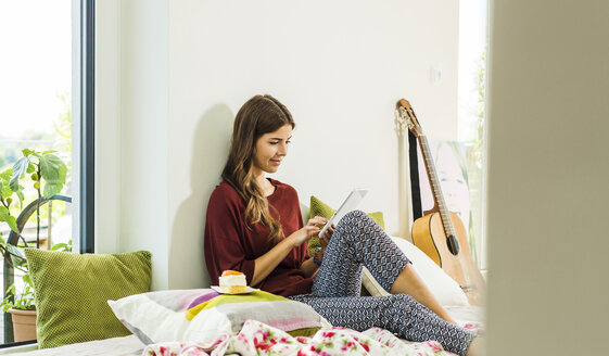 Relaxed young woman using digital tablet at home in bed - UUF004679