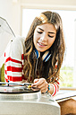 Young woman at home with record player - UUF004684