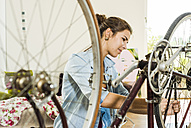 Young woman at home repairing her bicycle - UUF004691