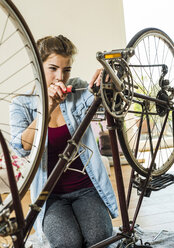 Young woman at home repairing her bicycle - UUF004693