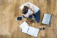 Student sitting on wooden floor surrounded by papers, laptop, digital tablet, file folder, coffee and fruit bowl - UUF004698