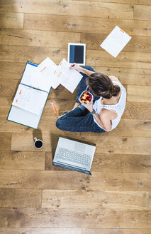 Student sitting on wooden floor surrounded by papers, laptop, digital tablet, file folder and coffee - UUF004699