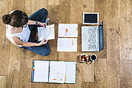 Student sitting on wooden floor surrounded by papers, laptop, digital tablet, file folder, coffee and fruit bowl - UUF004700