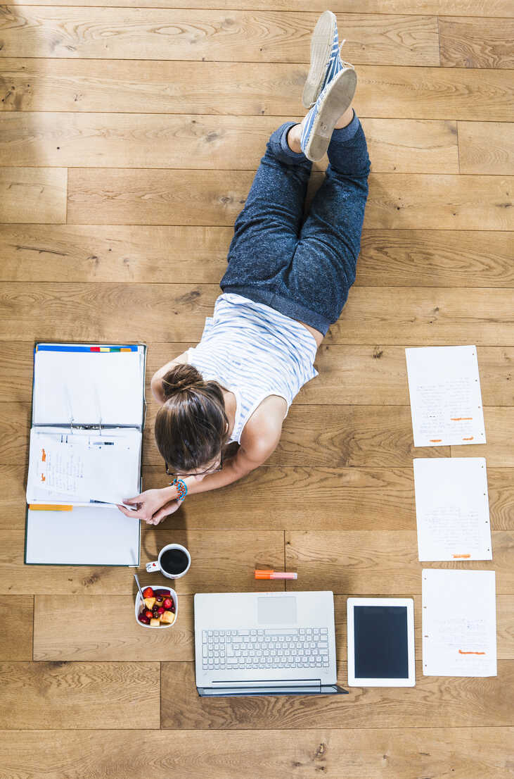 Student lying on wooden floor surrounded by papers, laptop, digital tablet, file folder, coffee and fruit bowl - UUF004742 - Uwe Umstätter/Westend61