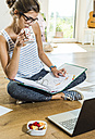 Young woman sitting on wooden floor with file folder and laptop - UUF004744