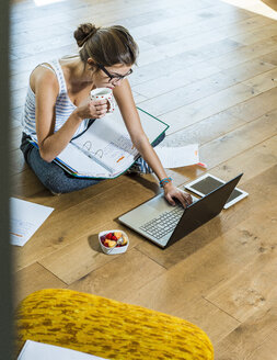 Young woman sitting on wooden floor with file folder and laptop - UUF004746
