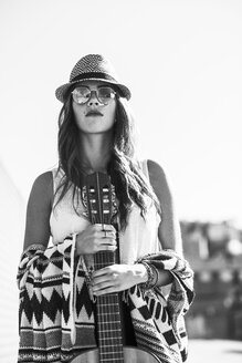 Young woman wearing boho style holding guitar - UUF004711