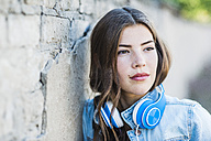 Brunette young woman with headphones leaning against brick wall - UUF004724