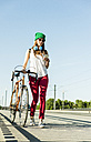 Young woman with bicycle on pavement looking at cell phone - UUF004727