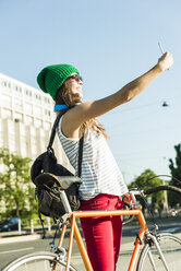 Smiling young woman with bicycle on pavement taking a selfie - UUF004729