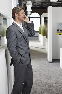 Businessman in office on smartphone - PDF000984