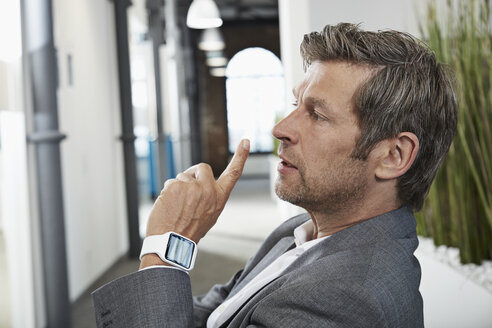 Businessman in office with smartwatch - PDF000979