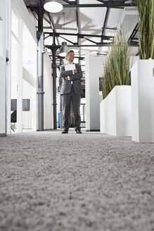 Smiling businessman standing in modern office - PDF000985