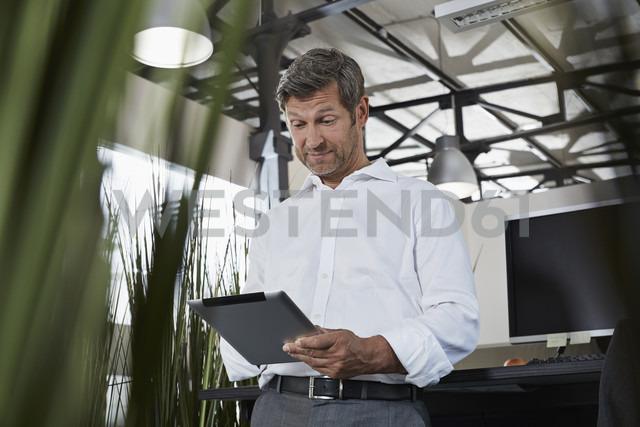 Surprised businessman in office looking at digital tablet - PDF000989