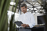 Surprised businessman in office looking at digital tablet - PDF000989