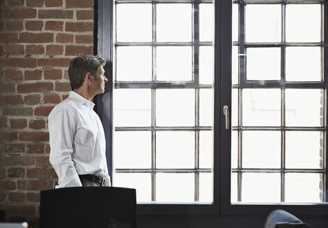 Businessman in office looking out of window - PDF000998