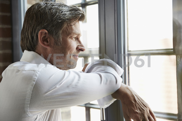 Businessman looking out of window - PDF001002