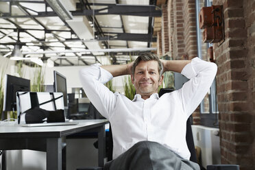 Portrait of smiling businessman in office relaxing - PDF001003