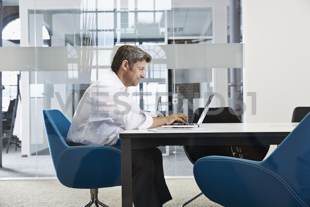 Businessman using laptop in conference room - PDF001011