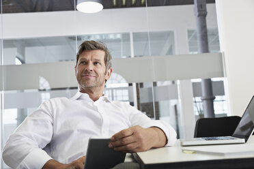 Businessman in office with digital tablet and laptop - PDF001014