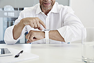 Businessman in office looking at smartwatch - PDF001069
