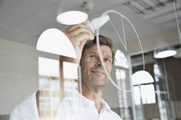 Businessman drawing diagram on glass pane in office - PDF001032