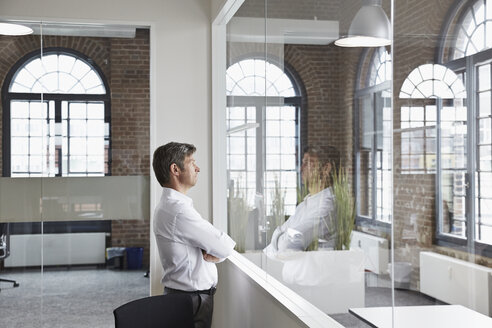 Businessman in office standing at glass pane - PDF001038