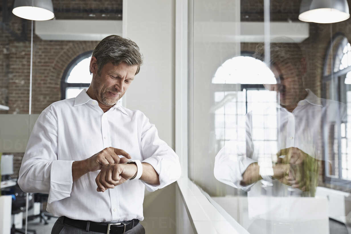 Smiling businessman in office looking at smartwatch - PDF001071 - Philipp Dimitri/Westend61