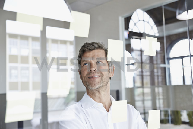 Businessman with sticky notes on glass pane in office - PDF001044