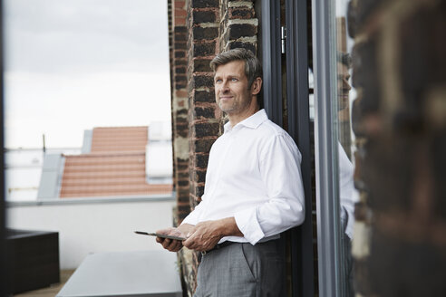 Smiling businessman with digital tablet on roof terrace - PDF001050