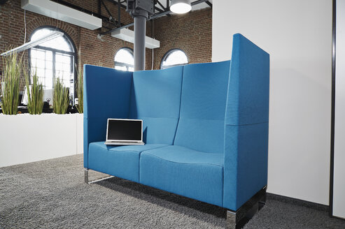 Laptop on noise protected conversation pit in modern office - PDF001064