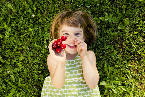 Smiling little girl with cherries lying on a meadow - LVF003500
