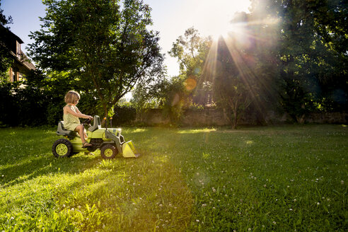 Little girl playing with toy tractor in a garden - LVF003503