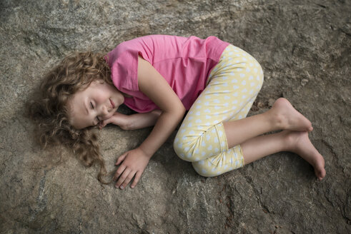 Girl lying on rock with closed eyes - MW000089