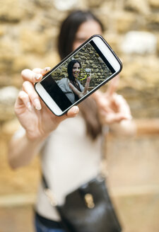 Smartphone with photo of smiling woman taking a selfie - MGOF000289