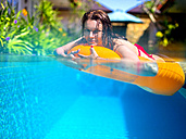 Young woman with floating tire in a pool - KNTF000065
