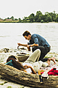 Young couple having a barbecue by the riverside - UUF004760