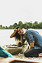 Happy young couple having a barbecue by the riverside - UUF004762
