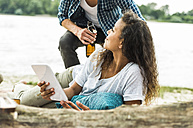 Smiling young couple with digital tablet outdoors - UUF004775