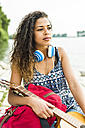 Young woman with headphones, guitar and backpack by the riverside - UUF004790