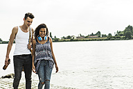 Young couple walking by the riverside - UUF004792
