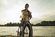 Young man with bicycle and cell phone by the riverside - UUF004817