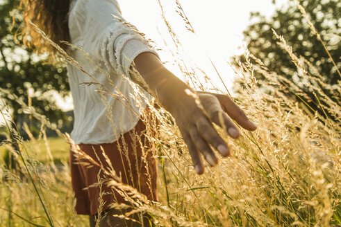 Woman touching tall grass in field - UUF004825