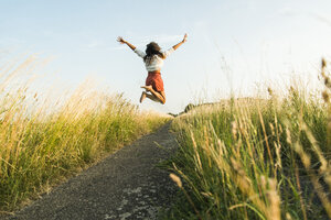 Enthusiastic young woman jumping on path in field - UUF004835