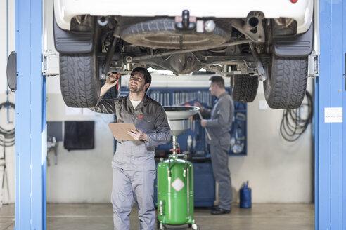 Two car mechanics at work in repair garage - ZEF005687