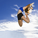 Young athlete jumping under blue sky - STSF000813