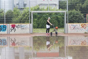 Senior woman with wheeled walker on sports ground - SGF001672