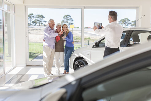 Car dealer taking picture of happy family with car key - ZEF006342
