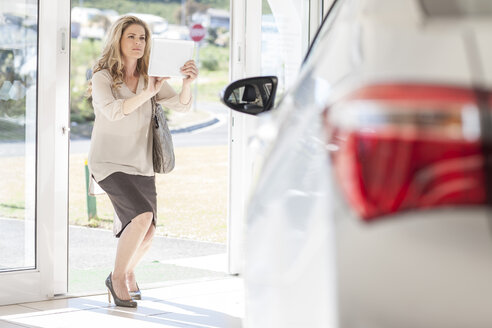 Woman taking picture of a new car in showroom - ZEF006352
