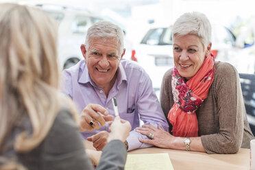 Smiling senior couple at car dealer - ZEF006382